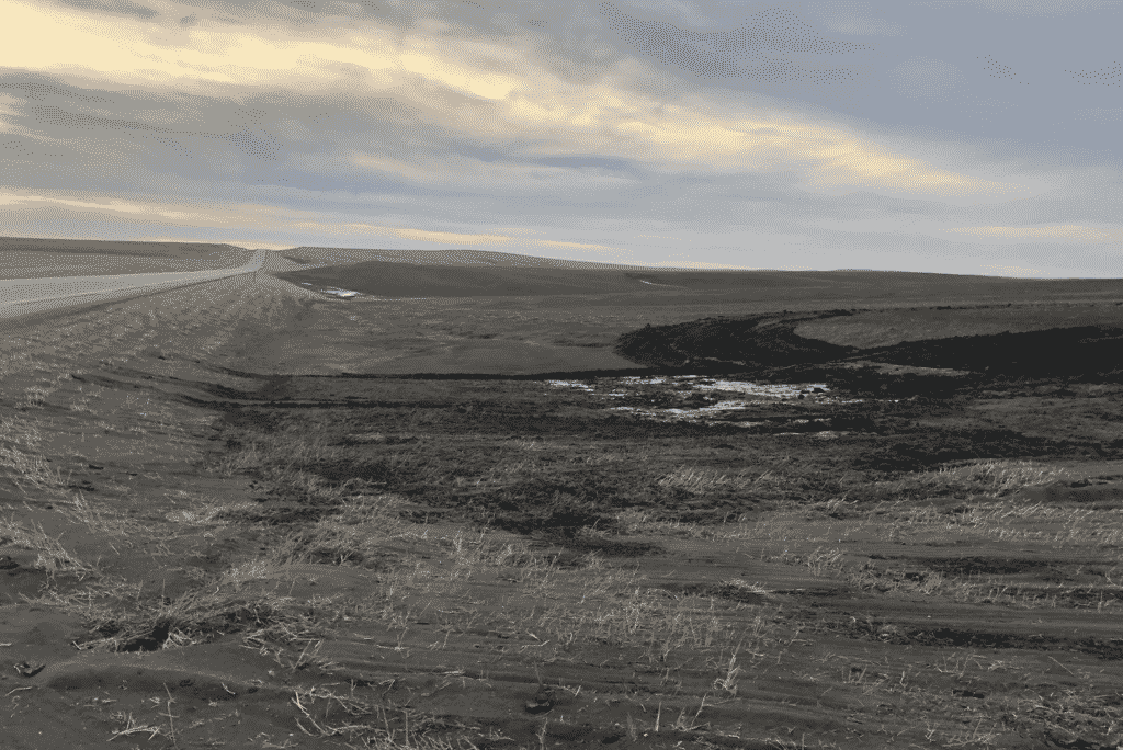 Wind-blown soil fills a ditch between a road and the fields of Gunsmoke Farm, a large organic farm northwest of Pierre, S.D., in early March. Source: NPR, 2021.